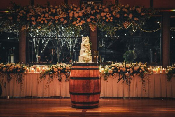 Adelaide Wedding Photographers - Wedding Cake on Wine Barrel with floral installation at National Wine Centre